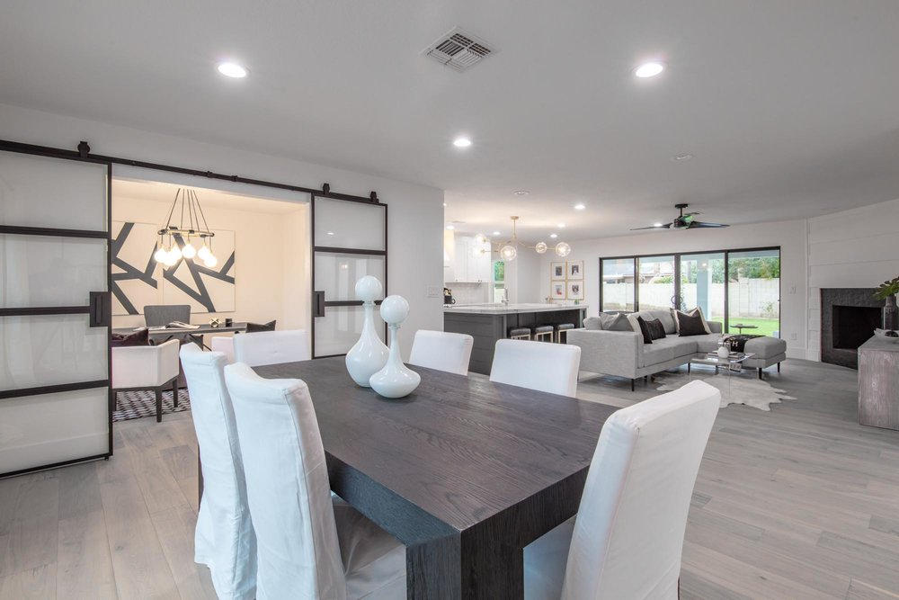 Dining area with wooden rectangular table for six and white chairs