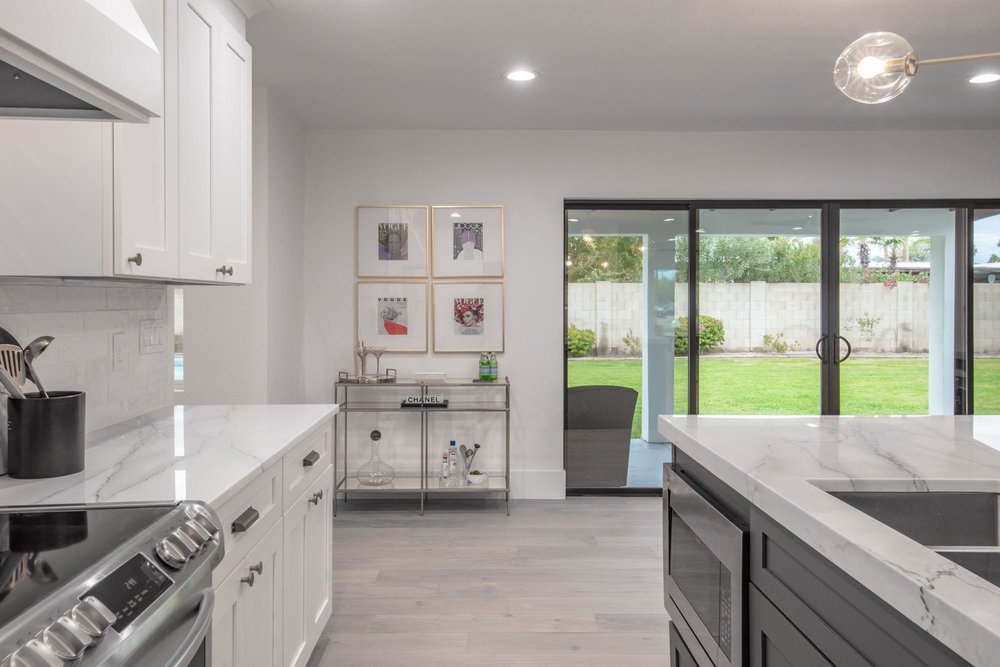Kitchen area with large windows viewing lawn garden