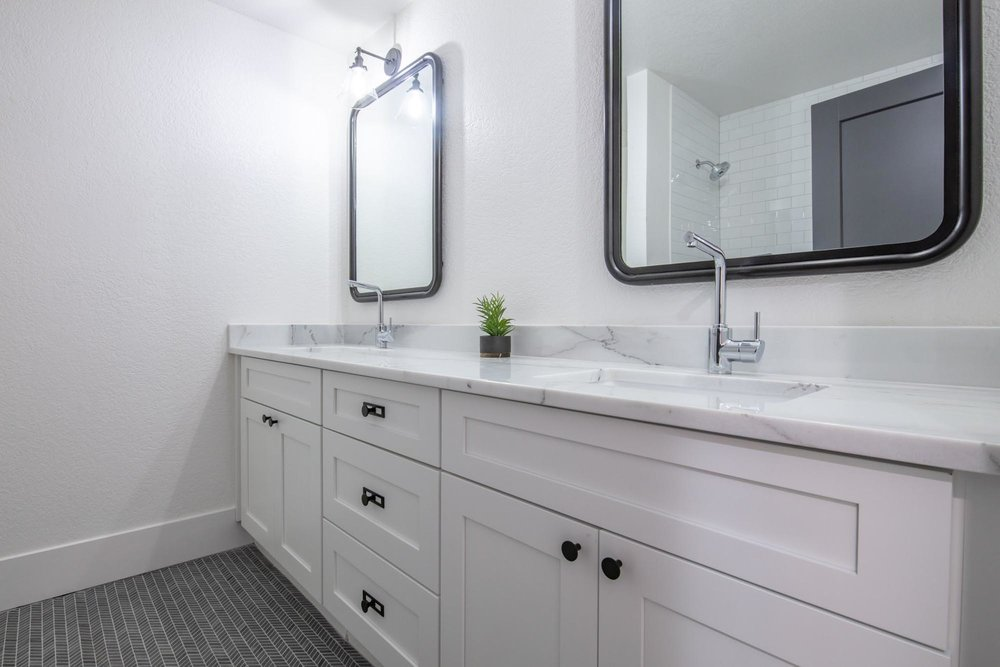 Washroom with two large mirrors and white cabinet