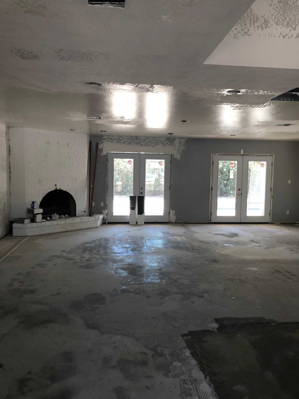 Ongoing room renovation with large windows and fireplace