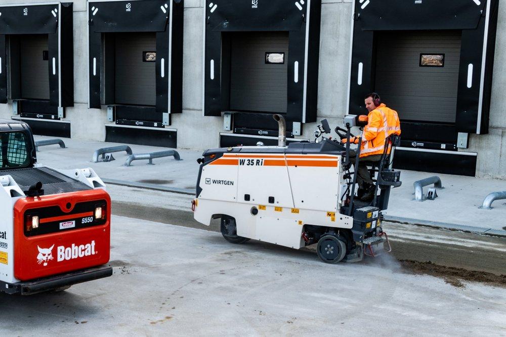 Frezen - Met frezen halen we oneffenheden uit het asfalt of beton en maken we plaats voor een nieuwe laag. Ook kunnen bijv. wortelopdrukken worden verwijderd.