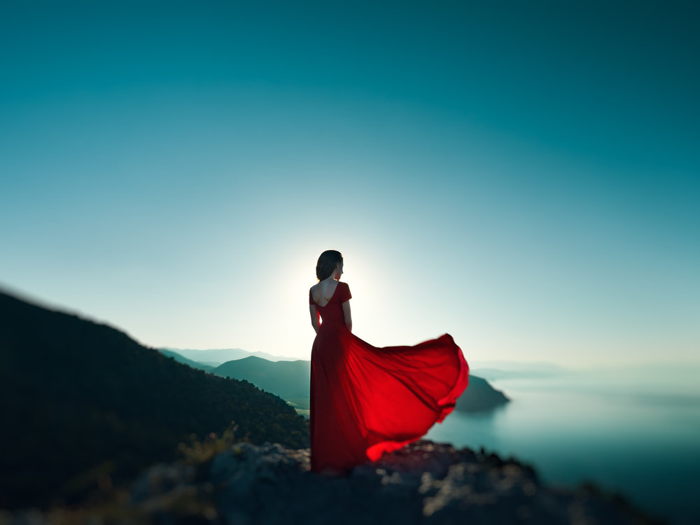 young-beautiful-woman-in-red-dress-looking-to-PYQ36D3.jpg