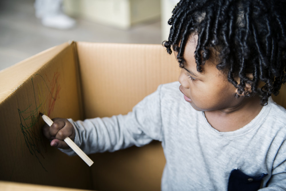 young-black-boy-drawing-in-a-box-P5XKD6S.jpg