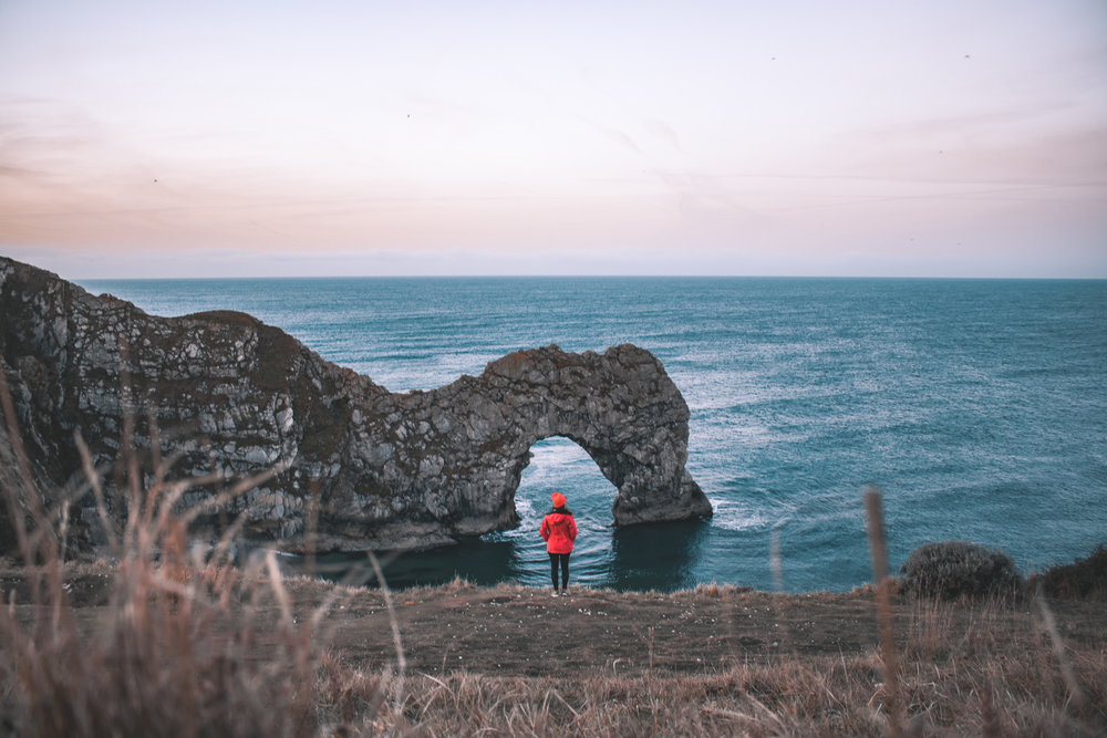 Durdle door sunrise with a girl