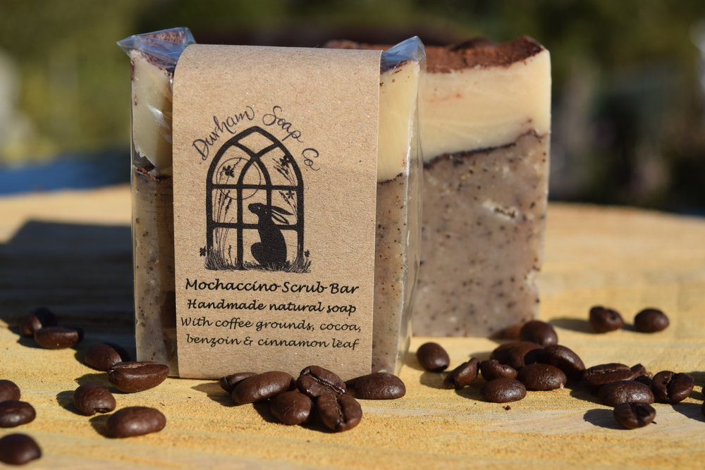 Mochaccino Scrub - Natural scrub soap, handmade with our blend of pure plant oils, enriched with moisturising shea butter, cocoa butter and castor oil for a rich and creamy lather. Our soap is fragranced with a warming blend of cinnamon and benzoin essential oils and infused with ground coffee beans and cocoa powder to create a delicious sweet and spicy scent. The coffee grounds add a gentle scrub, making this soap ideal for use by gardeners or for use in the kitchen. Ingredients: Olive oil, coconut oil, sunflower oil, shea butter, cocoa butter, water, castor oil, benzoin oil, Coffee arabica brewed coffee grounds, cocoa) powder, cinnamon oil, Vitamin E, Benzyl benzoate*, Benzyl cinnamate*, Eugenol* * occurs naturally in essential oils.