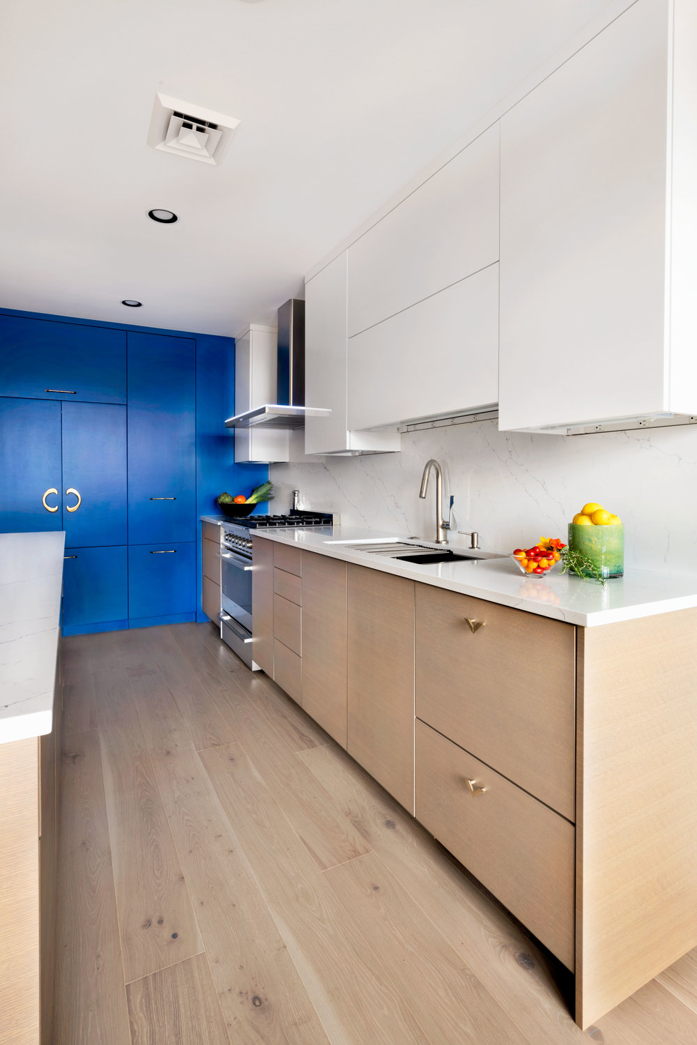 Modern finishes and color pop in the narrow kitchen.