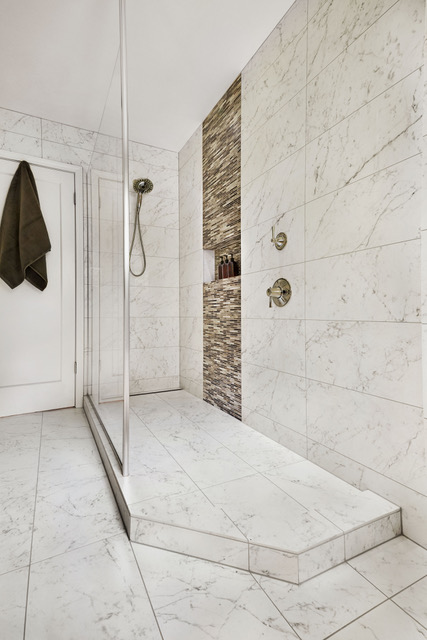Spacious new walk-in shower with linear drain and large-format marble look flooring.
