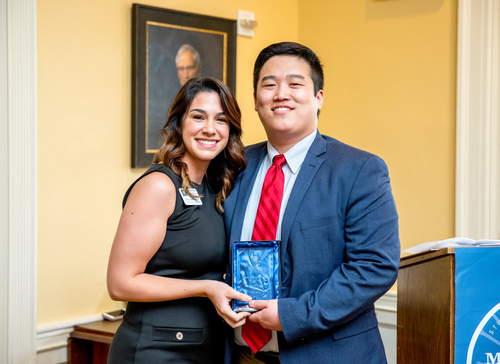 IMPACT Student of the Year Wei Lin accepts his Head Program Director of the Year Award at Madison House's annual Legacy of Service reception.