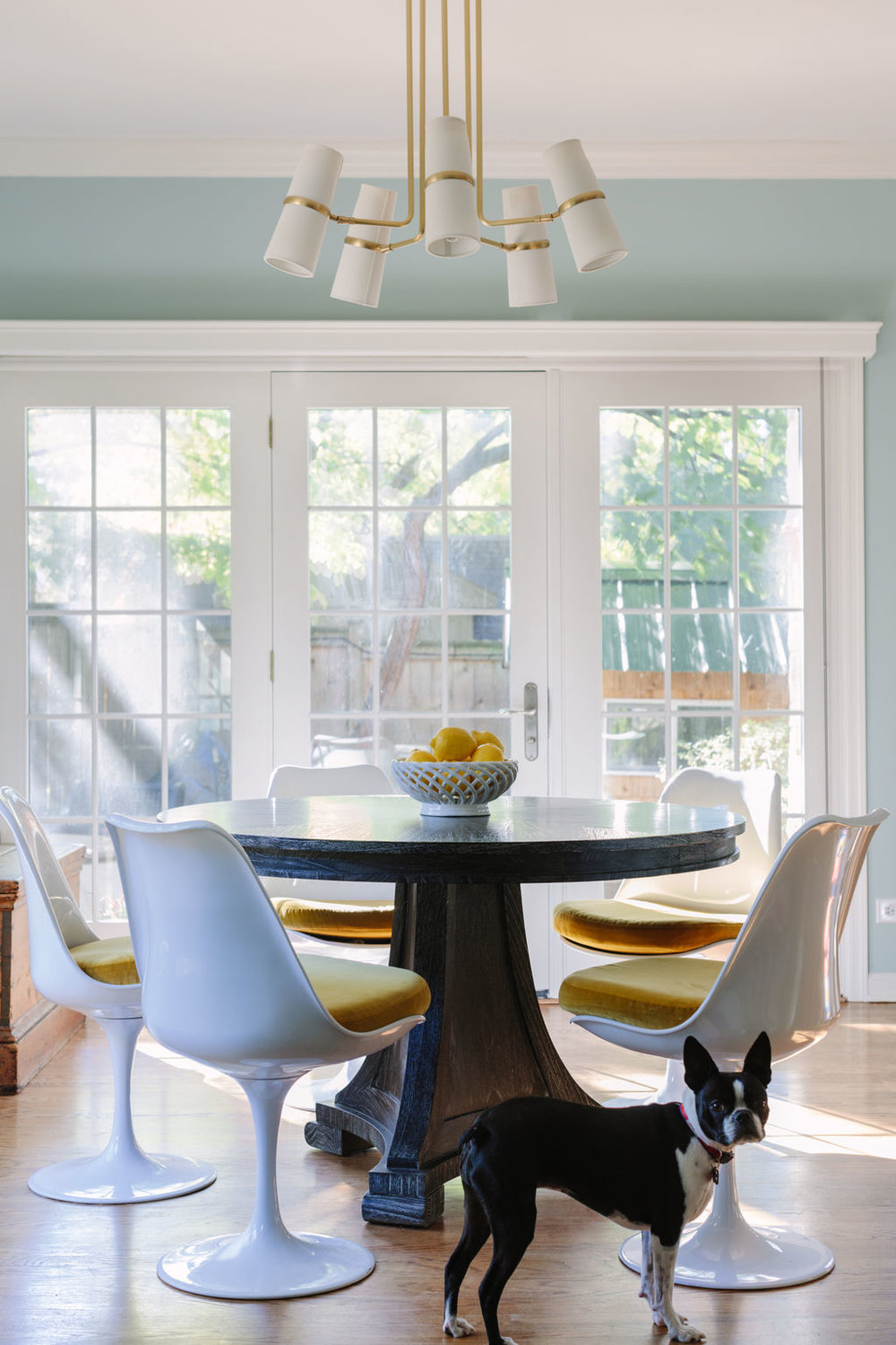 Chicago interior designer White tulip chairs with Bugalow 5 wood breakfast table and Rejuvenation light