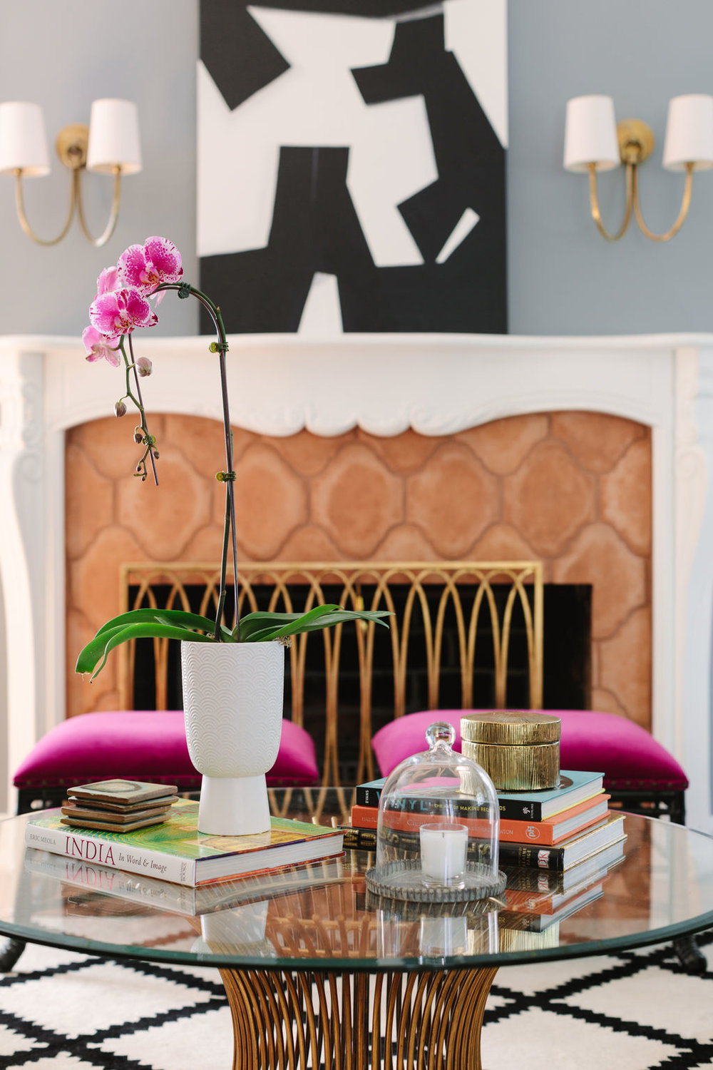 Chicago interior designer Circa Lighting sconces, black and white art, World's Away gold and glass coffee table, Horchow fireplace screen