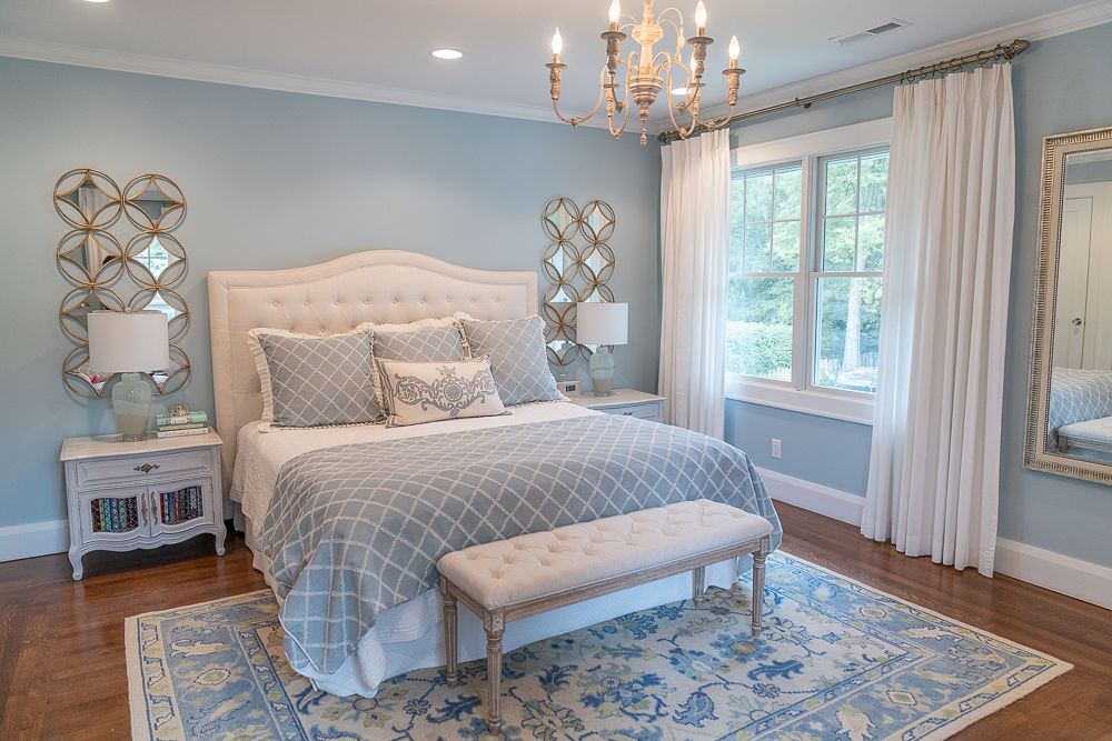 Blue painted bedroom with large bed, chandelier and table