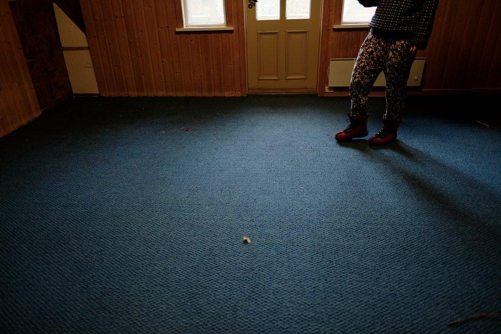 Gudrun viser og her korleis ein bør kle seg når ein arbeider i stort hus. Her i kledd raude ulltøflar mamma-stil, buksa med blomar på, og prikkete ullgensar. På hovudet har ho grøn hua.