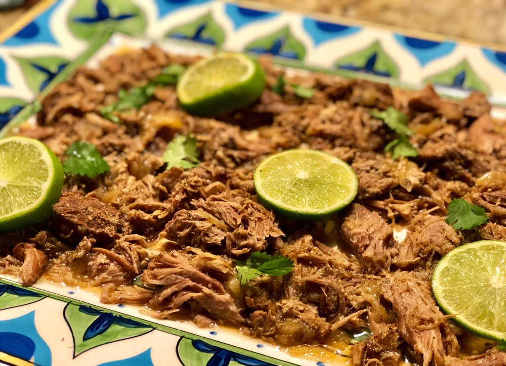 Cooked pressure cooker pulled pork on a plate topped with sliced limes and cilantro.