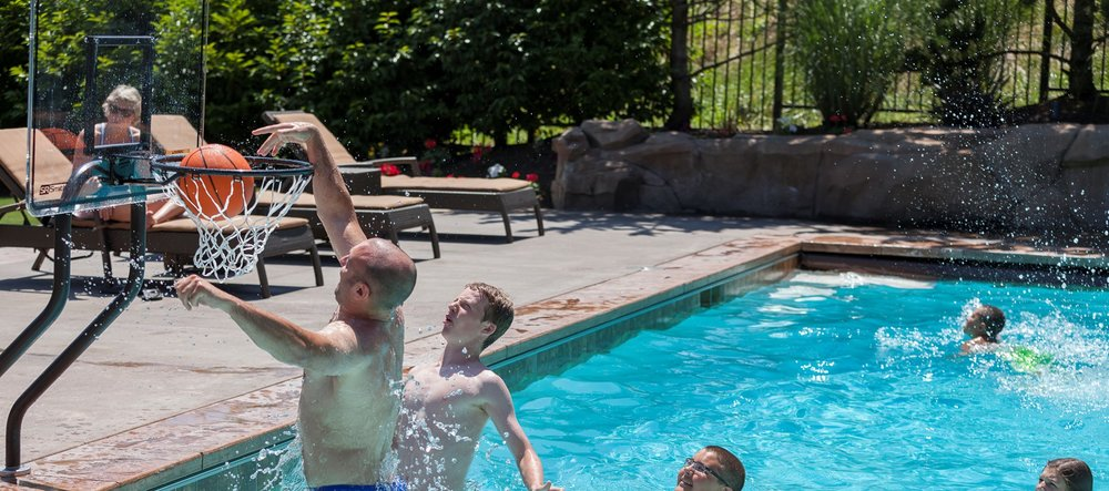 A family playing water basketball with a goal from S.R. Smith.
