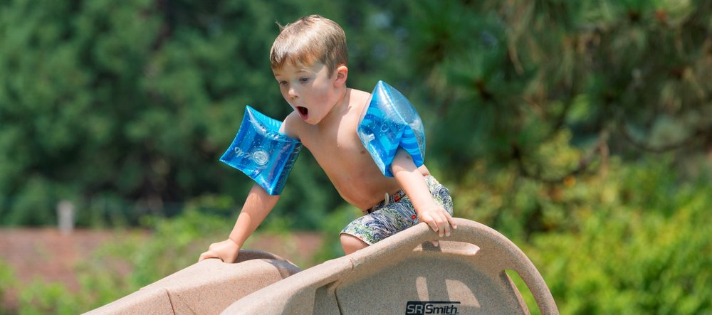 A young boy wearing arm float gets ready to go down a slide in his family's backyard pool.