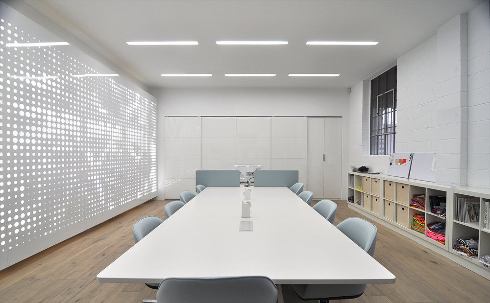 The metal panels are offset from the wall, allowing space for lighting behind.