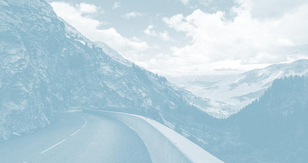 Mountain road, mountain vista and sky. Photograph by Alex Talmon.