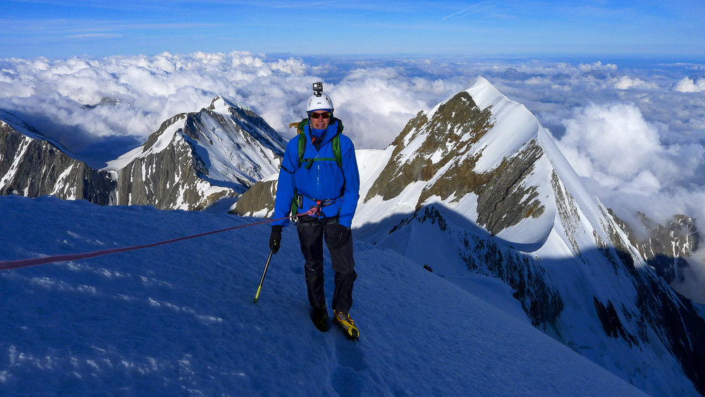 Dave on the Pope Route. The Aiguille du Bionnassay traverse climbs the very narrow crest in the background.