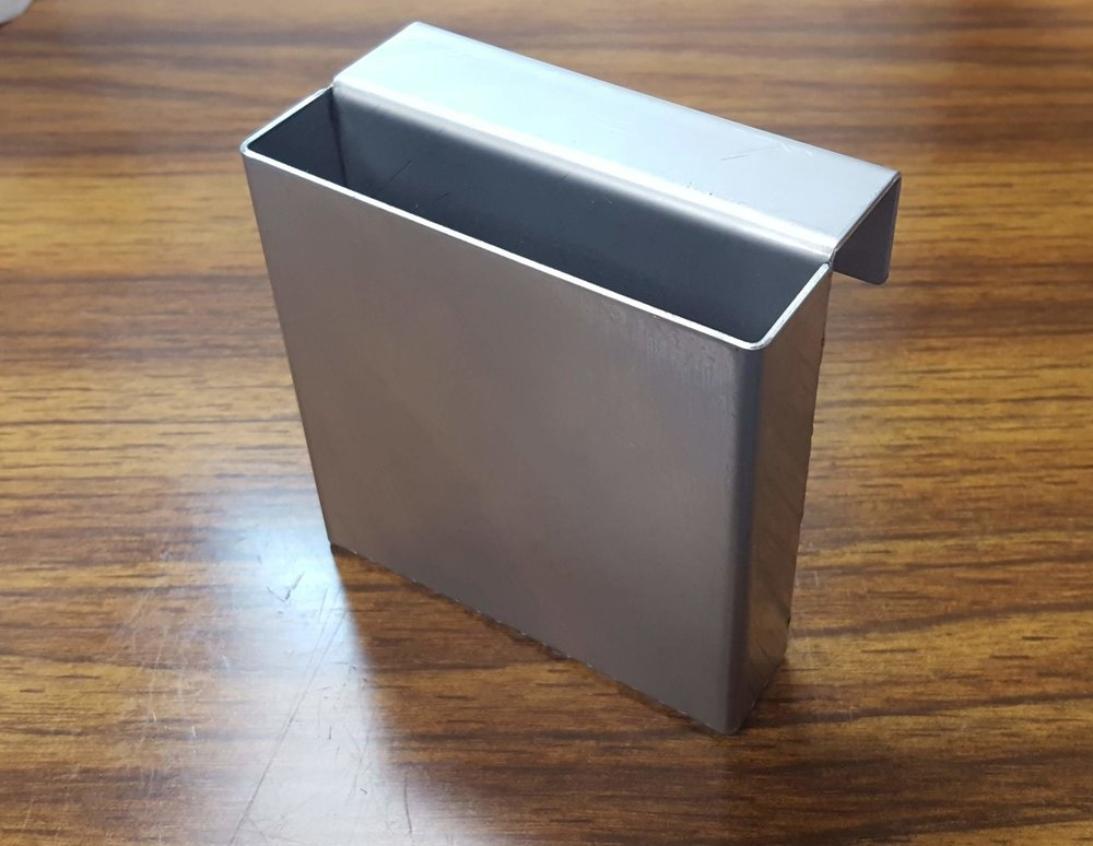 A formed and welded stainless steel container with perforated metal bottom for drainage.