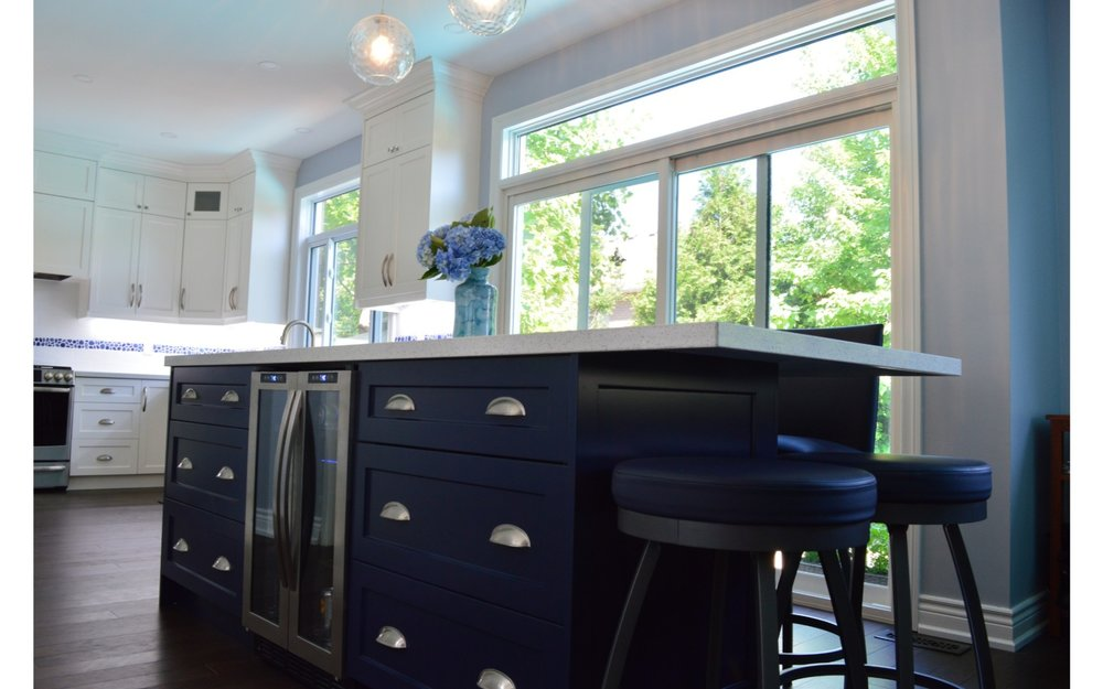 Kitchen island with blue cabinets and built in wine fridge