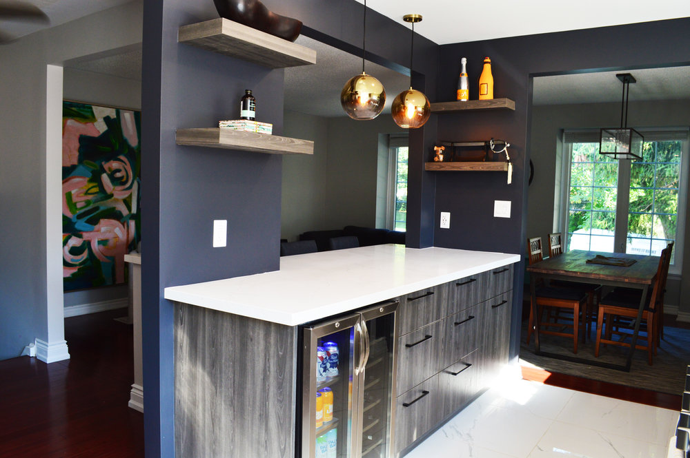 Bar with grained grey cabinets and built in beverage fridge