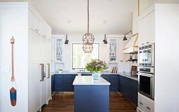 Light kitchen with hanging lights, blue cabinets and white countertops