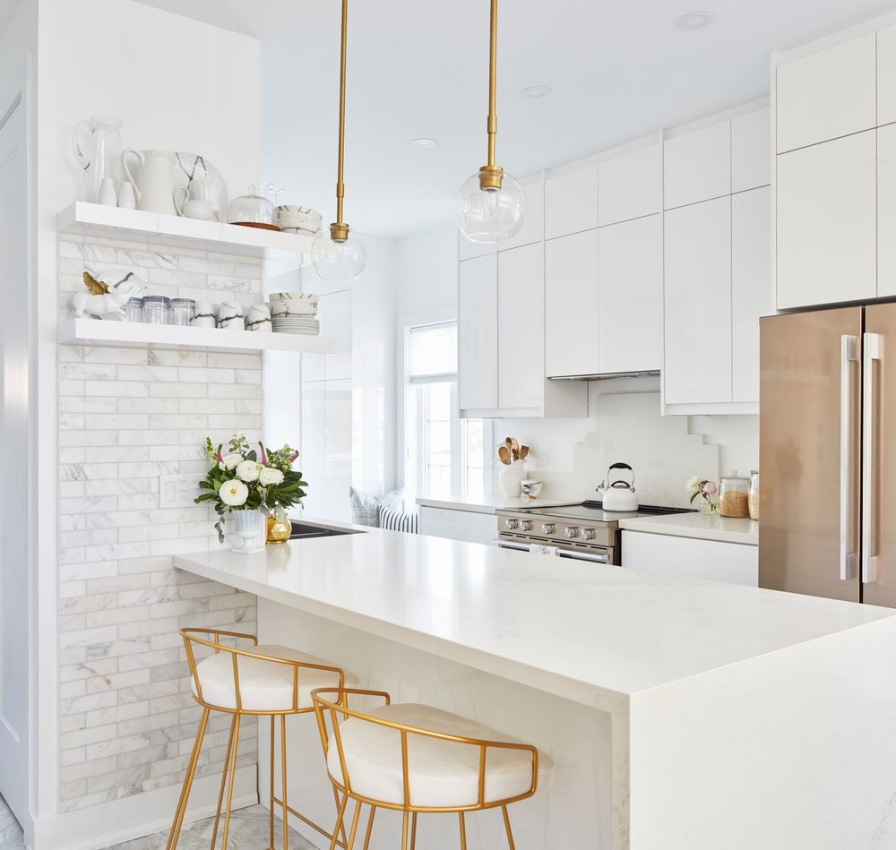 Bright kitchen with light floors, cabinets, and countertops with brass fixtures
