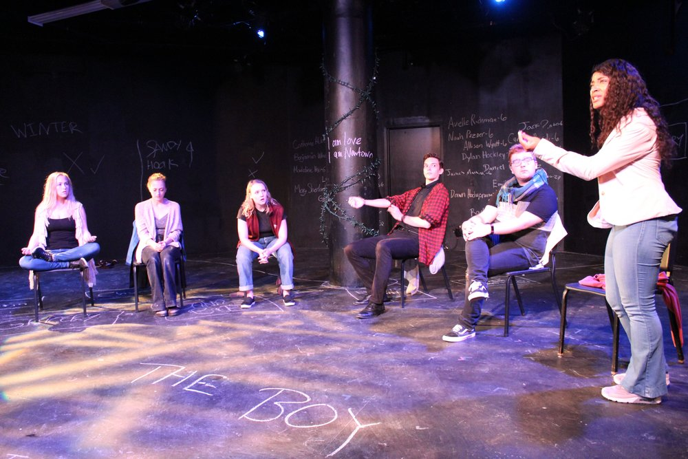 """The actors gather in a town hall to discuss Adam Lanza. The moment centers around a difficult discussion of whether we must subtract the perpetrator from our grief in order to heal and move on, or if that subtraction in itself is part of the problem. In the end, we chose to have Rabbi Praver, played by actor Dillon McGuire, write the names of Adam and his mother by the memorial wall in a desperate attempt to """"be together."""" This moment is immediately followed by Joe, a former art teacher at Sandy Hook who is also played by McGuire, angrily discussing how the town needs to forget them. At the height of his monologue, he goes to the wall and smears Nancy and Adam Lanza's names. In doing this we hoped to echo the sentiment of the town hall, where certain community members attested that there were 28 victims that day and that the town was responsible for letting Adam """"fall through the cracks"""", while also honoring the plays title and acknowledging the deeply complicated nature of morality and the human spirit."""