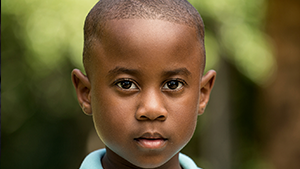 [Image] A young elementary-aged male child from the neck up with brown eyes standing outside, representing a child of Voices for Children CASA. Voices for Children CASA of Boulder County provides trained,  C ourt  A ppointed  S pecial  A dvocate Volunteers to advocate for the needs of abused and neglected children in Boulder County.