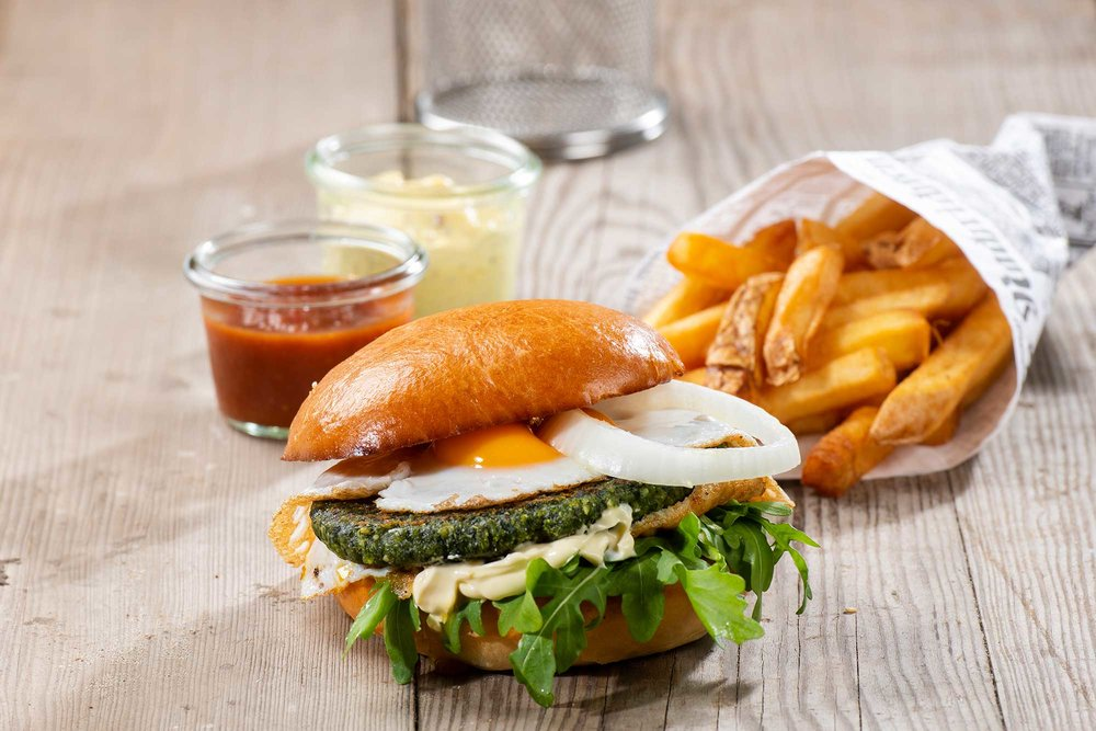 Veggie Burger - Brioche, Spinat-Käsepatty, Mayonnaise, Zwiebelringe, zwei Spiegeleier