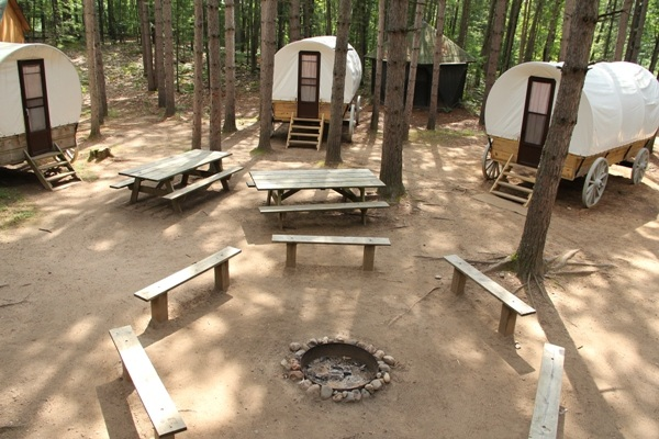 Pioneer Village - - Consists of four covered wagons, each containing four single beds- Located in a pine forest