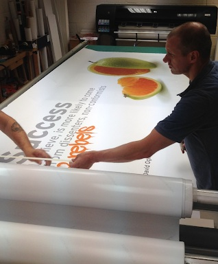 Some of our print team preparing large format graphics for a wall, after it was printed.