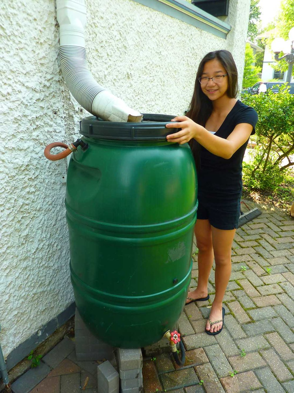 A girl checks her rain barrel.