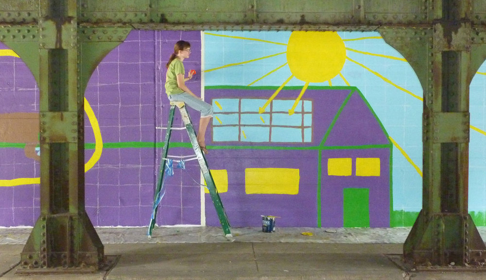 Helen Files sits atop a ladder at the Kenilworth underpass in Oak Park. Her portion of the Girl Scout mural encourages people to use solar panels.