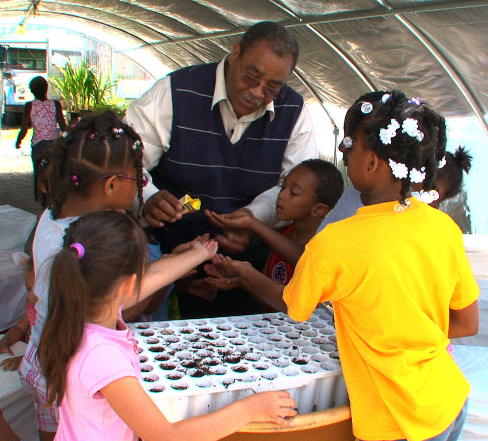 Michael Howard shows children how to grow with seeds.
