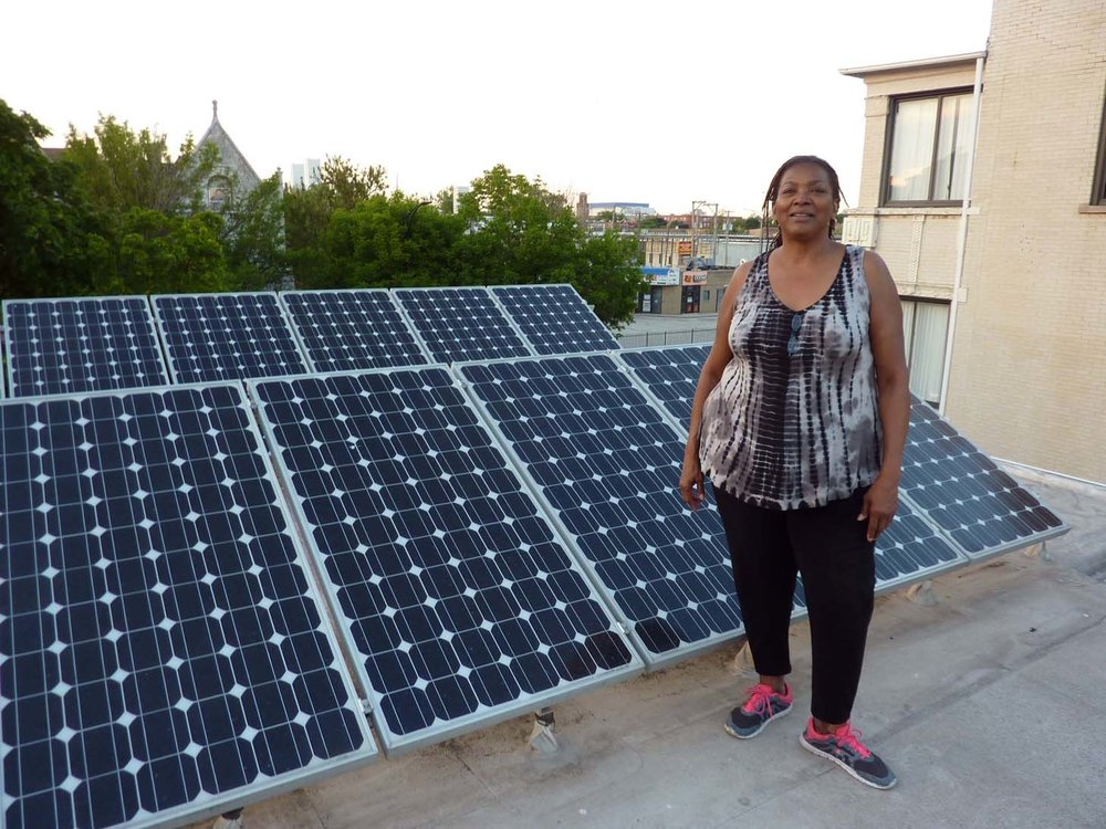 Annette stands next to her rooftop solar panels.