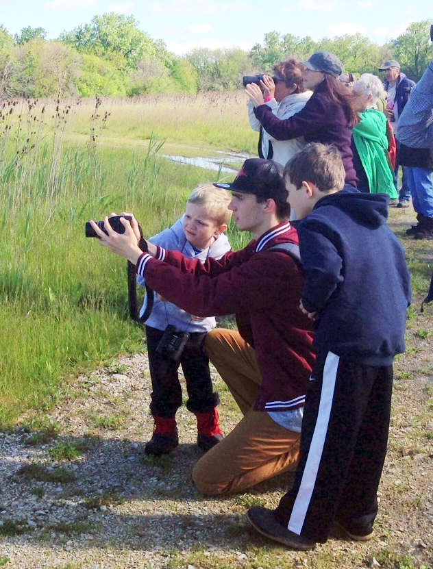 Henry helps two young birders find a Bobolink perched in the meadow.