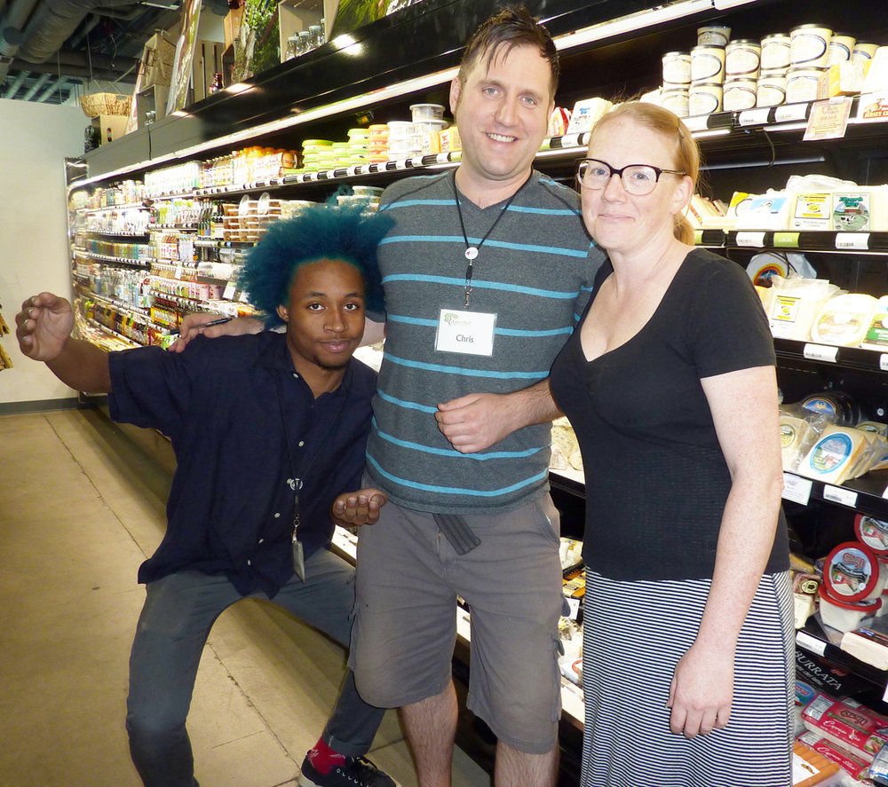 Stocking clerk John Smith, General Manager Chris Roland, and Marketing Director Lissa Dysart convene in the deli aisle.