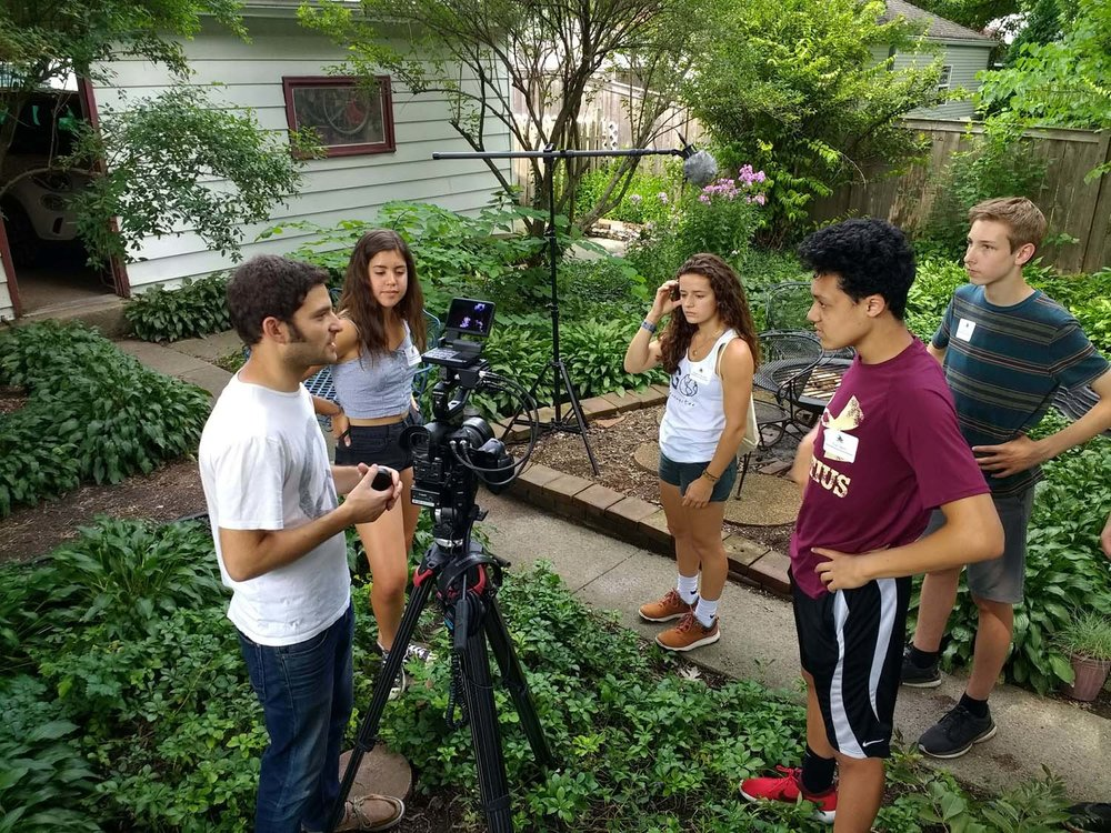 Matt Wechsler of Hourglass Films helps students prepare for an outdoor interview in Estelle Carol's lush garden.