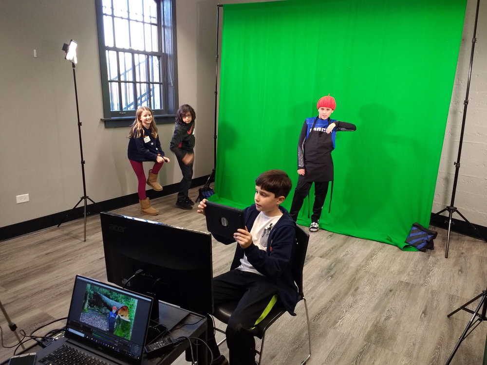 Students in grades 3 through 5 use their iPads and cell phones to shoot footage for narrative films about environmental topics at the River Forest Park District Depot on December 9.