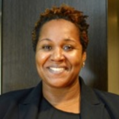 Image: Keisha, smiling, with curly short brown hair, wearing a black blazer and blouse.