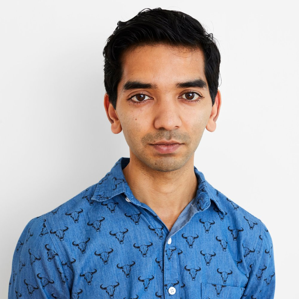 Image: Waqas, with black short hair, wearing a blue button-down shirt.
