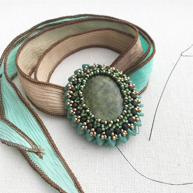 The first photo is the back of the pendant, and I think it looks better than the front...sometimes that happens 😬. It could just be a reversible pendant. Now, how should I attach it to the silk ribbon... #beads #bezeledstone #silkribbon #seedbeads #beadinspiration #trianglebeads #mint #seafoamgreen #mintombre #mintchocolate #colorway #madeinalaska #modernbeadwork #beadlove #newfanglednorth