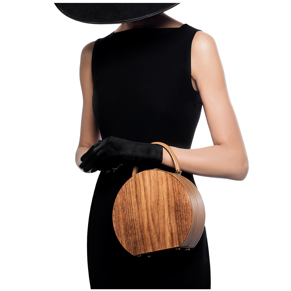 BUMI Leather & Walnut - A unique blend of American walnut wood and Italian calf leather, created in the singular size. It is the ideal timeless keeper for any occasions to carry your values. The interior provides two pockets, created as one — one hidden and one with snap closure. It comes with a detachable graceful shoulder strap.Dimensions: Height 20 cm; Width 22 cm; Depth 8 cm;Price: from 4500 EUR