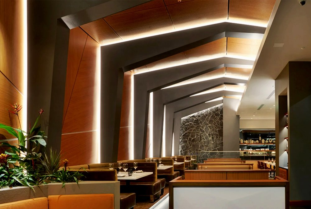 Stripsteak Waikiki - Location: Honolulu, HIType: Restaurant & BarSize: 8000 sq ftHow do you approach the design of a steakhouse in Honolulu's new International Market Place, that doesn't draw from the usual Hawaiian cliches, but still exudes island charm?Watch a British spy movie, of course.Stripsteak Honolulu began with Bond, James Bond, and references the famous modernist architecture of every villains' secret lair. Be it on a remote desert island, or hidden inside a volcano, the mid-century styling of the villain's lair feels right at home in this tropical paradise, while adding a subtle nod to the romanticized Hawaii of the 1960's.