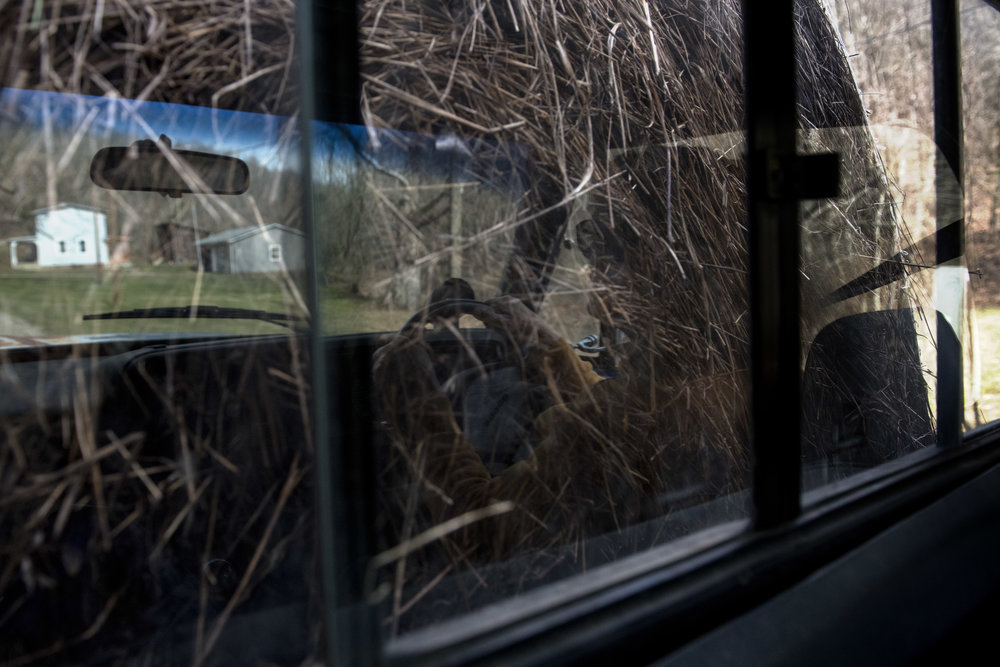 Reflections are caught in the back window of Heidi Marty's truck, against the textures of hay.
