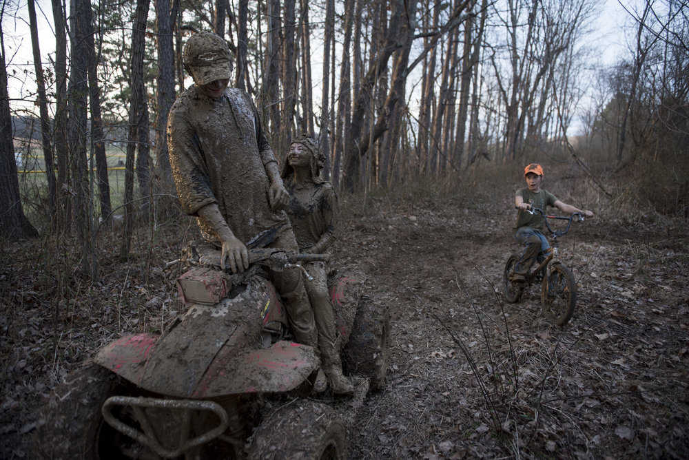 "Cameron Powell and Ivy Meeks share a laugh on Cameron's father's four wheeler after a mud fight while Elijah Bowers trails behind. After seeing them return from the mud, a friend said, ""If I had a nickel for every time I was covered in mud, I'd be a rich man."""