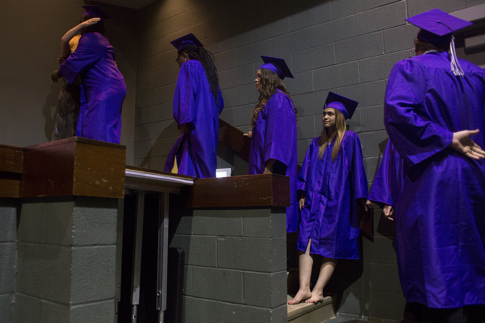 "After taking off her heels because of a blister, Brooke waits to walk on stage at graduation at AIS Diamond High School on May 22, 2018. ""I was really nervous, but once I took my shoes off, I didn't have anything to be nervous about,"" Brooke said."