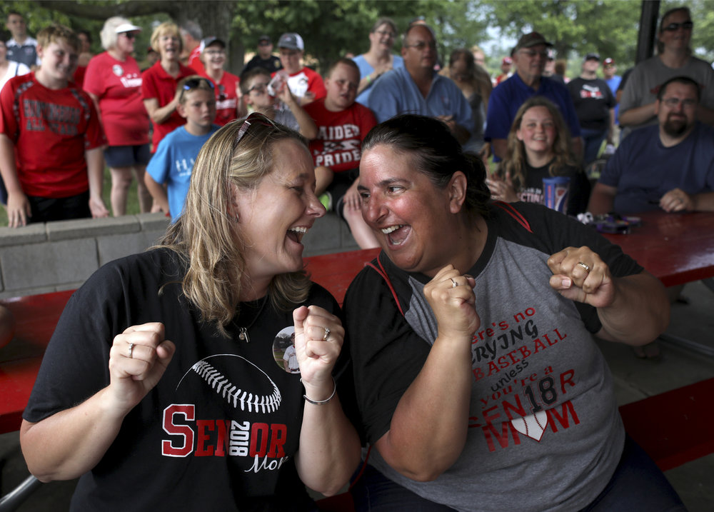 "Jill Harter, left, mother of Southridge High School baseball senior Jayce Harter, and Staci Smith, mother of Southridge High School baseball senior Colin Smith, sang the Southridge High School song at the pep session at League Stadium in Huntingburg following the Raiders' Class 2A semistate victory in Jasper on June 9, 2018. Harter, who went to Southridge, joked about Smith, who went to Jasper, ""we've converted her."""