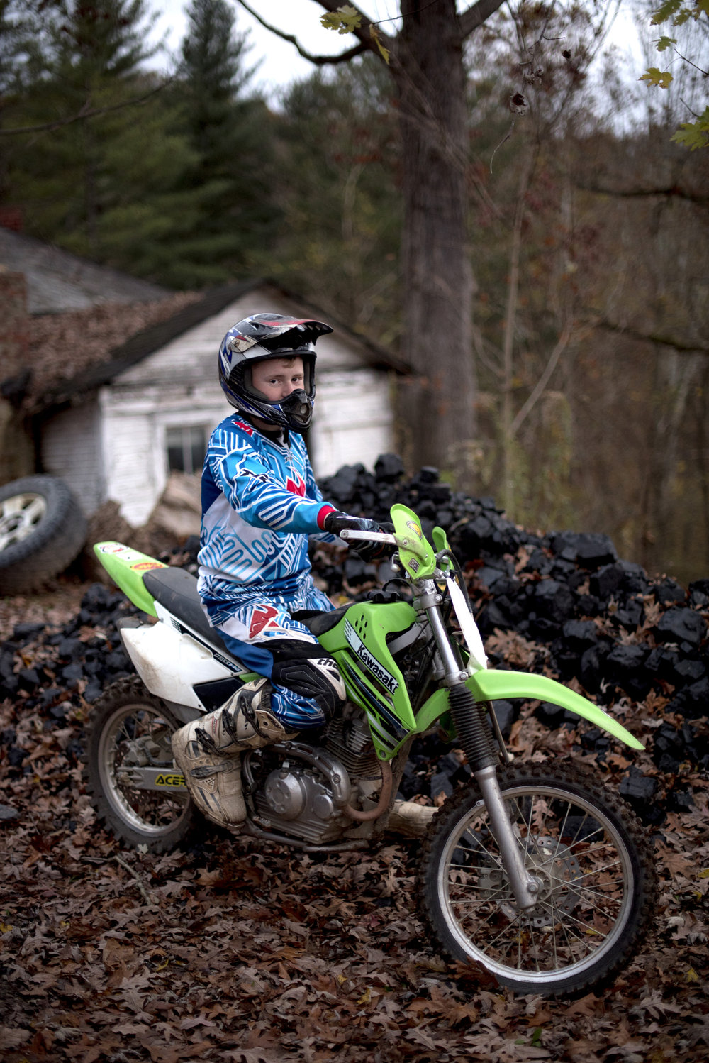 Christopher McDonald, 13, of Murray City, Ohio poses for a portrait on his dirtbike outside his home on Nov. 9, 2016. McDonald is entering his first dirtbike race this coming weekend. Behind McDonald is a pile of unprocessed coal that his family uses for heat in the winter. McDonald's father works at the Buckingham Coal Mine.